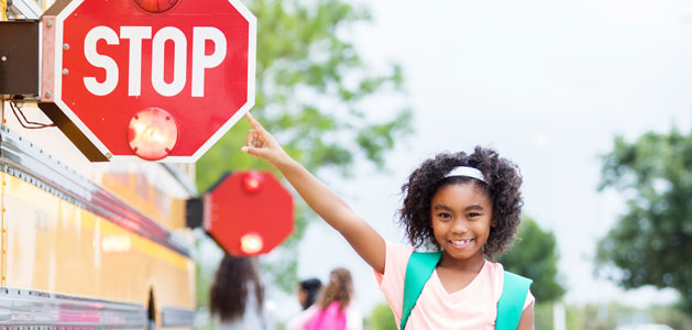 image of girl pointing to the stop sign on the side of a school bus